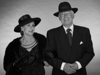 Vintage glamour senior couple wearing black hat. Black and white