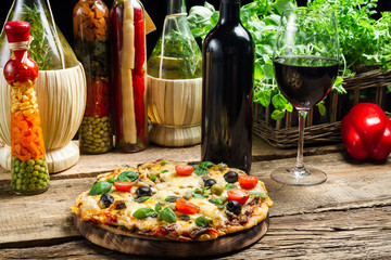 Baked pizza served with wine on the background of fresh vegetabl