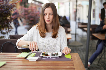 Young woman pouring soy sauce on sushi plate
