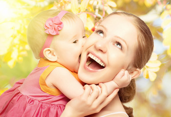 Happy cheerful family. Mother and baby kissing in nature outdoor