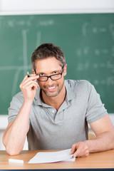 netter lehrer schaut über seine brille