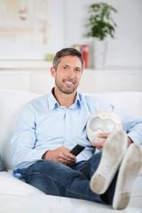 mann mit fußball und fernbedienung