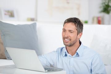 lächelnder mann mit laptop zu hause