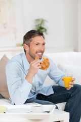 mann frühstückt auf dem sofa