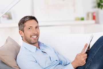 entspannter mann liegt mit tablet auf dem sofa