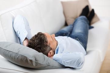 entspannter mann liegt auf dem sofa