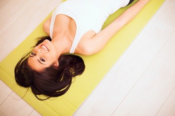 Young woman lying on the yoga mat and smiling