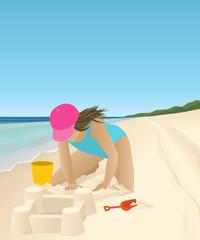 Girl on the beach building sand castle