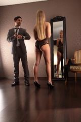 Mann zeigt neben Frau vorm Spiegel auf die Uhr