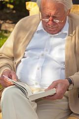 Senior man reading a book in garden in summer.
