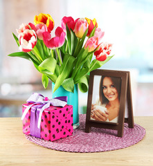 Beautiful tulips in bucket with gifts on table in room