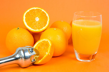 Glass of orange juice and a juice extractor