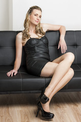 woman wearing black dress and pumps sitting on sofa