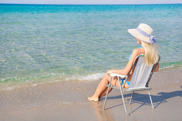 Blonde woman in white straw hat sitting on beach chair and look