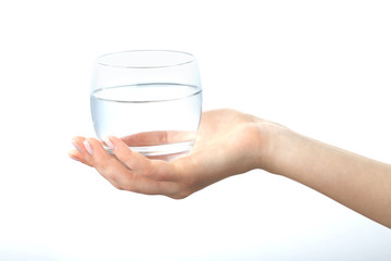 A hand holding a clear glass of water