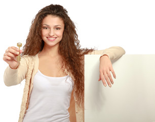 Portrait of a casual young woman holding blank card and key