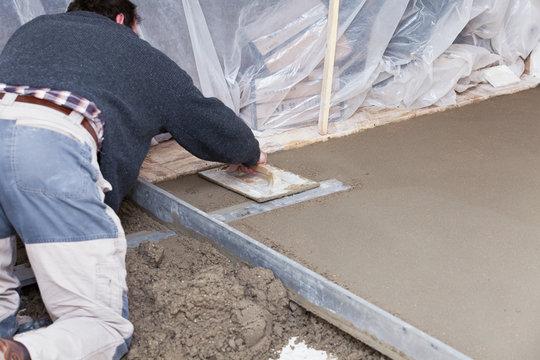 maçon qui prépare une chape en ciment