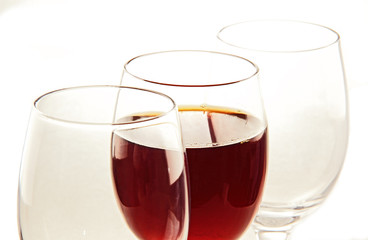 a glass of wine and empty glasses.