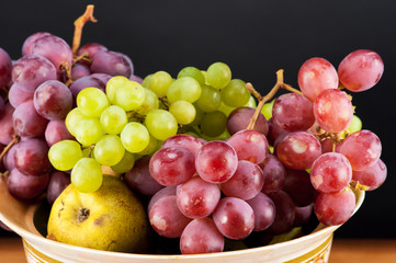 ripe grapes and pears in a bowl