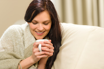 Smiling woman enjoying hot tea