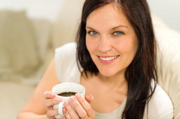 Smiling satisfied woman holding cup of espresso