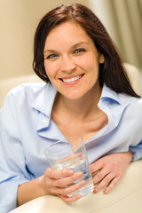 Joyful young woman holding glass of water
