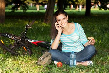 Девушка кушает в парке после езды на велосипеде