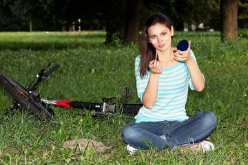 Девушка поправляет макияж на лужайке парка