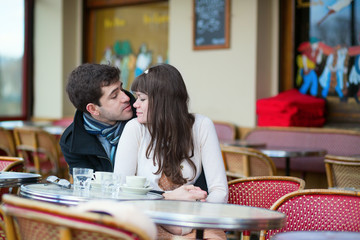 Dating couple kissing in a Parisian cafe
