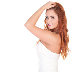 Beautuful woman with red long hair posing in white dress