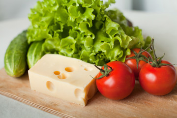 cheese and vegetables for salad on wooden board in the kitchen