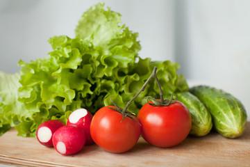 tasty tomatos, cucumbers, radish and salad on the kitchen