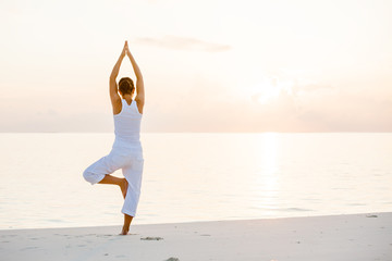 Tuinposter Ontspanning Caucasian woman practicing yoga at seashore
