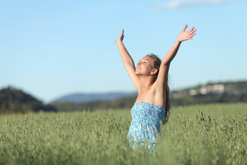 Woman with raised arms in a green meadow enjoying the wind