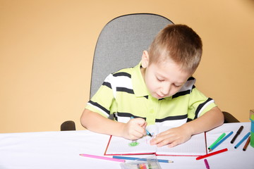 Young cute boy draws with color pencils