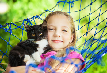 girl lies in a hammock with a cat in the open air