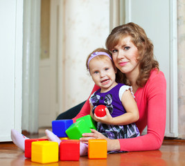 Happy mother and baby plays with blocks
