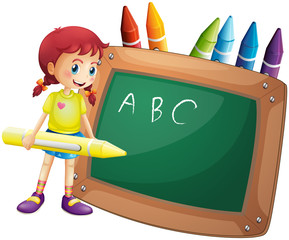 A girl holding a big crayon standing in front of a blackboard