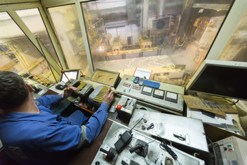 Worker looking on left in control cabin of rolling mill.