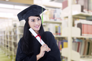 Asian graduate wearing graduation gown at library