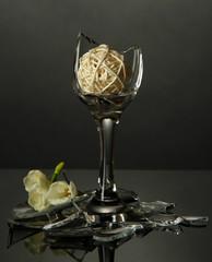 Broken wineglass with flower on grey background