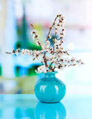 Beautiful blooming branches in vase on window background