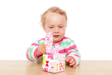 Baby girl unwrapping present.