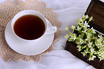 Composition with spring flowers and cup of tea