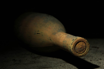 Old bottle of wine in old cellar, on dark  background