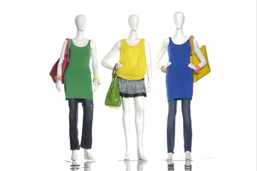 female colorful dress with bag on three mannequin