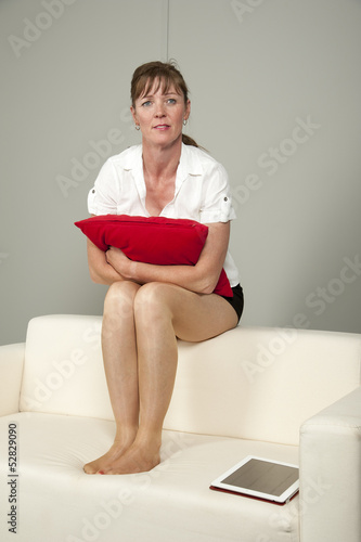 Woman wearing short skirt sitting on a sofa