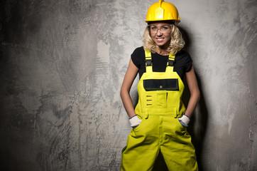 Fototapeta Attractive builder woman posing against grunge wall obraz