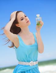 Redhead girl with perfume on the beach