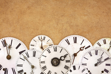 Set of vintage white clock faces against an old brown background